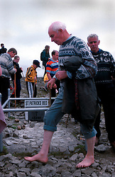 IRELAND CO. MAYO CORAGH PATRICK JUL99 - A bare-footed pilgrim walks around St. Patrick's suppsed grave on top of Croagh Patrick mountain in western Ireland. Around 25,000 people, some of which are bare-footed, participate in this pilgrimage to the top of Croagh Patick mountain on the last Sunday of July from where in 441 A.D. St. Patrick supposedly sent Ireland's reptiles to their doom. ..jre/Photo by Jiri Rezac..© Jiri Rezac 1999..Contact: +44 (0) 7050 110 417.Mobile: +44 (0) 7801 337 683.Office: +44 (0) 20 8968 9635..Email: jiri@jirirezac.com.Web: www.jirirezac.com..© All images Jiri Rezac 1999 - All rights reserved.