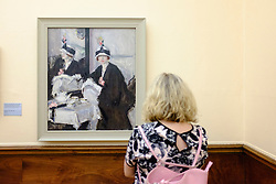 Visitor looking at painting Reflections by FCB Cadell  on display at Kelvingrove Art Gallery and Museum in Glasgow United Kingdom