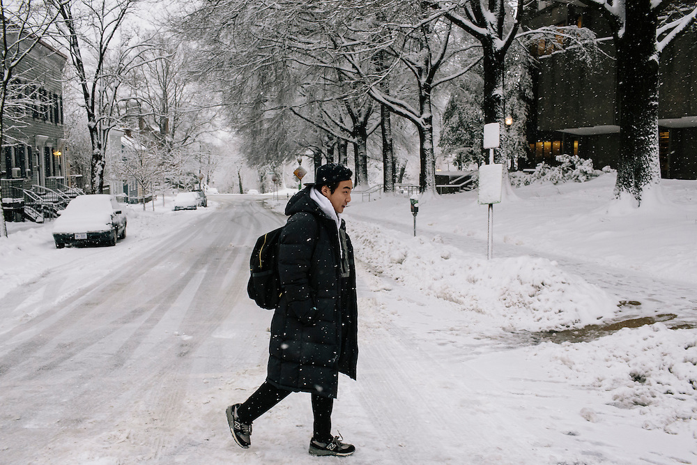 "Roy Kim, a Georgetown University sophomore, walks to the library during a snow storm to continue working on recording an English language track for his recording class. Kim became a South Korean pop star after winning Superstar K4, his country's version of American Idol. Kim says he is able to have a private life in the US without much fan interference. ""They know my life here should be respected,"" Kim said. ""That makes the relationship between me and my fans more tight."""
