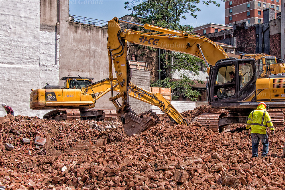 Link-Belt excavator trenching for lifting and moving material rock and soil. Blue collar workers at demolition of site for new building.