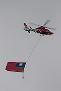 A rescue helicopter with a Taiwan flag does a flypast as part of the Republic of China (Taiwan) National Day celebration on October 10, in front of the Presidential Palace in Taipei.<br />