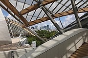 Staircase and terraces under the glass 'sails' of the Fondation Louis Vuitton, an art museum and cultural centre designed by Frank Gehry, b. 1929, and built 2008-14, next to the Jardin d'Acclimatation in the Bois de Boulogne, in the 16th arrondissement of Paris, France. In the distance are the towers of La Defense. The building resembles the sails of a boat and houses 11 galleries, an auditorium seating 350 and roof terraces. Picture by Manuel Cohen