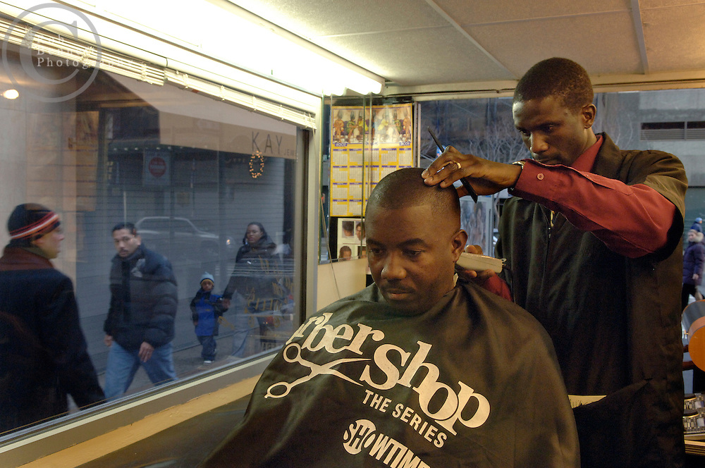 "8:25AM - Fulton Street and Hoyt Street - Downtown Brooklyn..Deon works on his first client of the day, 40 year-old Alfred Benjamin of Crown Heights - a security guard who had just wrapped up an overnight shift and was on his way home. ""It's convenient and he was in the correct spot,"" said Benjamin of the BOW service..--------------------------------------------..ÒIÕm like the ice cream man, only we donÕt sell ice cream, we sell haircuts.Ó..---..Deon Maynard wants to change the worldÉoneÉhaircutÉatÉaÉtime. ThatÕs right, by cutting hair. Spend a day with the man behind ÒBarbers on WheelsÓ and youÕll see that heÕs making some pretty good progress at it, too. Whether itÕs sprucing up the beard of a man on his way to a job placement program in downtown Brooklyn, laughing it up barbershop-style with theater executives outside of The Apollo in Harlem or putting smiles of the faces of passersby on Fordham Road in the Bronx, there seems to be something about this particular brand of innovation that gets in peoples bones and inspires them. ÒItÕs time people start to look at barbers differently,Ó says the 31-year old native of Barbados. ÒWe reface the entire world. We change appearances. When weÕre done, people think of themselves differently.Ó..Deon Maynard also wants to be rich. In fact, four months ago the Barbados native (his family moved to Flatbush when he was 2) created what he believes to be the first-ever ÒBarbershop on WheelsÓ to cash in on being Òwhere the action is.Ó After years of being weighted down by brick-and-mortar outlets throughout New York, the wheels beneath his barbershop now allow him to go wherever business is best, whenever it is best. Says Maynard, ÒI could be on the moon and cut hair. As long as thereÕs Martians with hair, IÕm gonna cut hair.Ó ..So, from dawn Ôtil well, well past dusk, Deon, alongside his driver and associate Philip White, roam the five boroughs and Western Long Island in a bakery truck whose interior has been stylishly, if not effi"