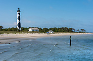 Establishing shot of Harkers Island as seen when arriving by Harkers Island Ferry. The Cape Lookout Lighthouse with its black diamonds on white appears to the left of the lighthouse keeper's quarters.