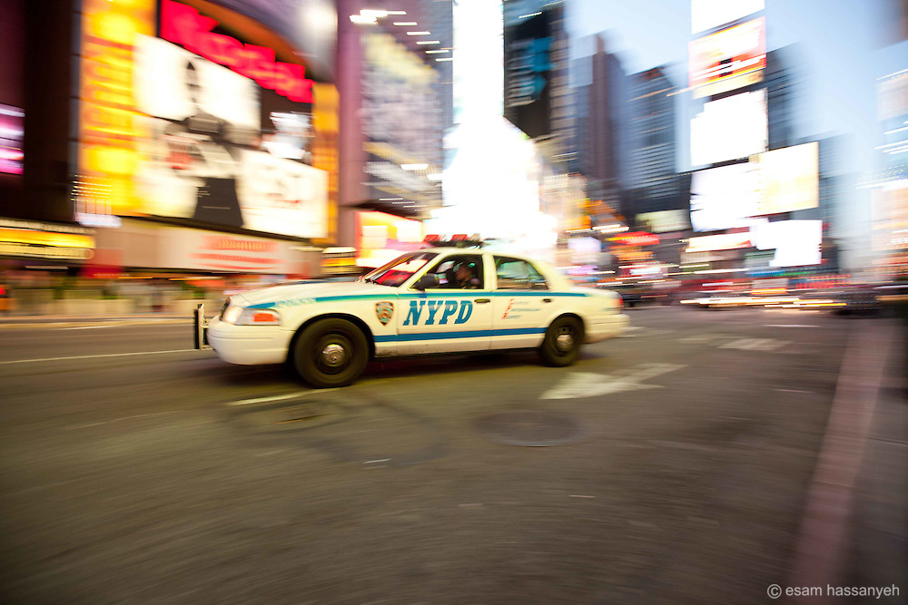 An NYPD car speeds through Times Square in New York