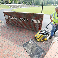 Murphee Paving employee Rusty Shaw continues to pack down asphalt around the edges of the track at Robins Noble Park on Madison Street Wwednesday. The City of Tupelo is in the process of resurfacing the track at the park as years of neglect.
