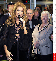 © Andre Pichette/ABACA. 38319-9. Montreal-PQ-Canada, 26/09/2002. Singer Celine Dion answers to questions as herparents Adhemar and Therese stand behind, after unveiling her bronze star at he Walk of Fame during a ceremony.