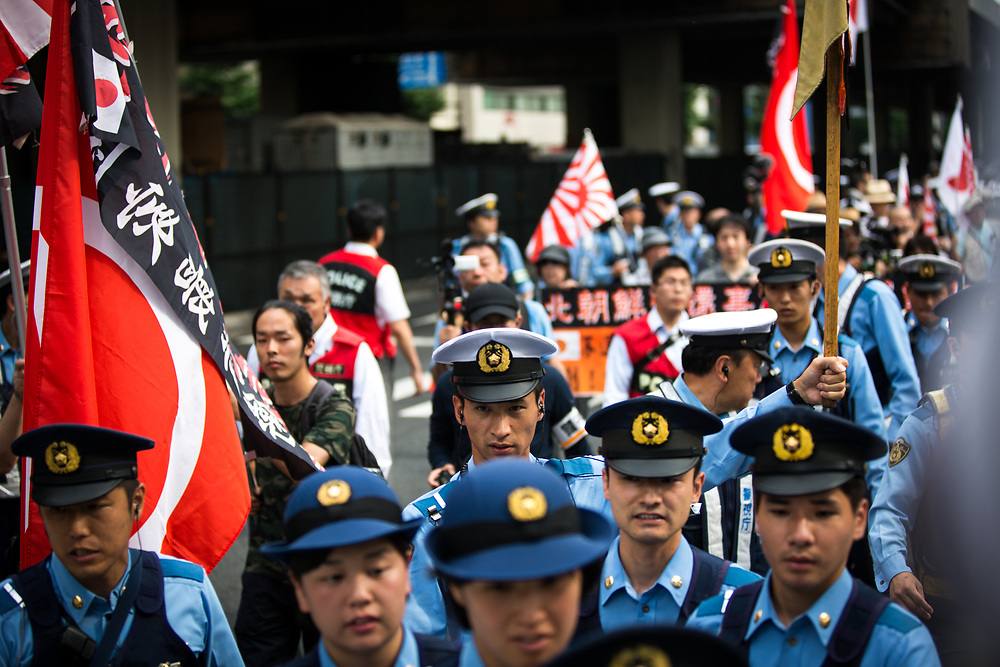 """TOKYO, JAPAN - JULY 16: Japanese nationalists holding Japanese maritime flags, escorted by police, took to the streets in a """"hate demonstration"""" in Akihabara, Tokyo, Japan on July 16, 2017. The nationalists faced off with anti-racist groups who mounted counter protests demanding an end to hate speech and racism in Japan. (Photo by Richard Atrero de Guzman/AFLO)"""