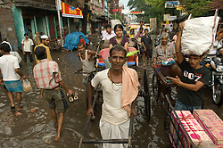 Kolkata's rickshaw pullers work through the flooded streets of central Calcutta around Chittaranjee Street September 13, 2007. This congested city was the first city of the colonial British and  now it is the only city of India where hand pulled rickshaws are still being pulled. In 1996, the Government of West Bengal announced that it was intending to ban the rickshaws to relieve traffic congestion  but it never was fully enforced. In 2007, the government again pushed to have the ban enforced and a case is currently being decided in the Supreme court that will determine the outcome for the hand pulled rickshaws.