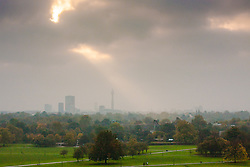 Primrose Hill, London, October 30th. The sun begins to break through as mist shrouds London's skyline, as dog walkers and fitness fanatics enjoy Primrose Hill. Pictured: The sun begins to break through, casting a shaft of light over Regents Park.