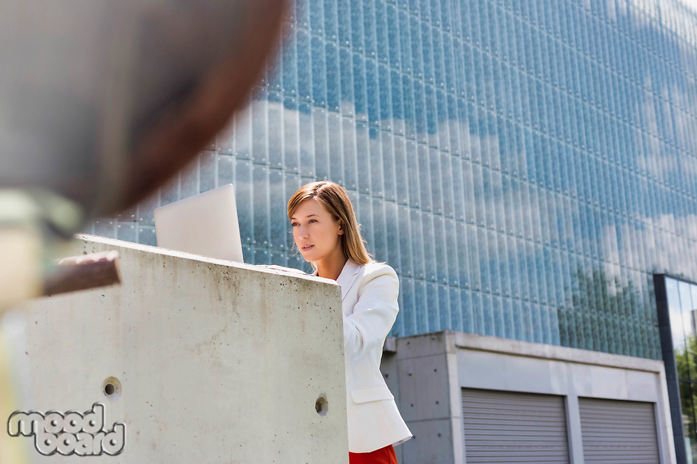 Portrait of young attractive businesswoman working on her laptop outdoor