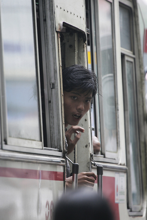 A Rangoon bus worker watches for potential fares during traffic in downtown Rangoon.