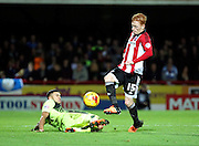 Brentford midfielder Ryan Woods dinking the ball over a Huddersfield Town player to start another Brentford attack during the Sky Bet Championship match between Brentford and Huddersfield Town at Griffin Park, London, England on 19 December 2015. Photo by Matthew Redman.