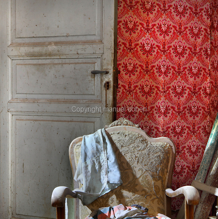 A room in an abandoned building in a state of dereliction with an antique chair and red floral wallpaper, in the old town or Casc Antic of Tortosa, Tarragona, Spain. Tortosa is an ancient town situated on the Ebro Delta which has a rich heritage dating from Roman times. In recent years, many buildings in the old town have been abandoned and fallen into disrepair. Picture by Manuel Cohen