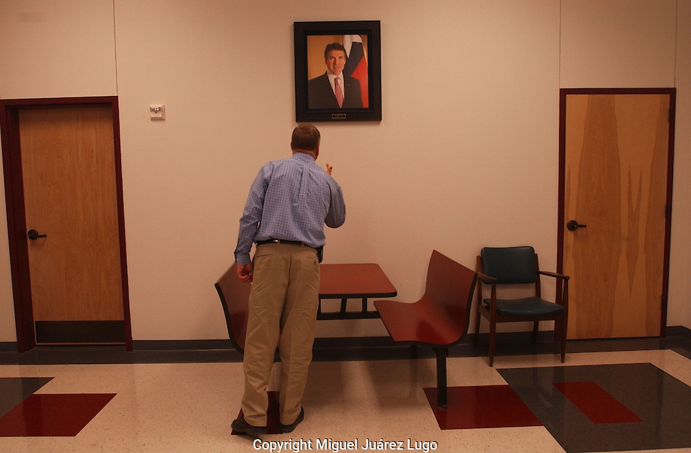 Paint Creek school district superintendent  Don Ballard shows a photograph of Governor Rick Perry hanging in a school hallways.  Perry graduated from the school. (PHOTO: MIGUEL JUAREZ LUGO).