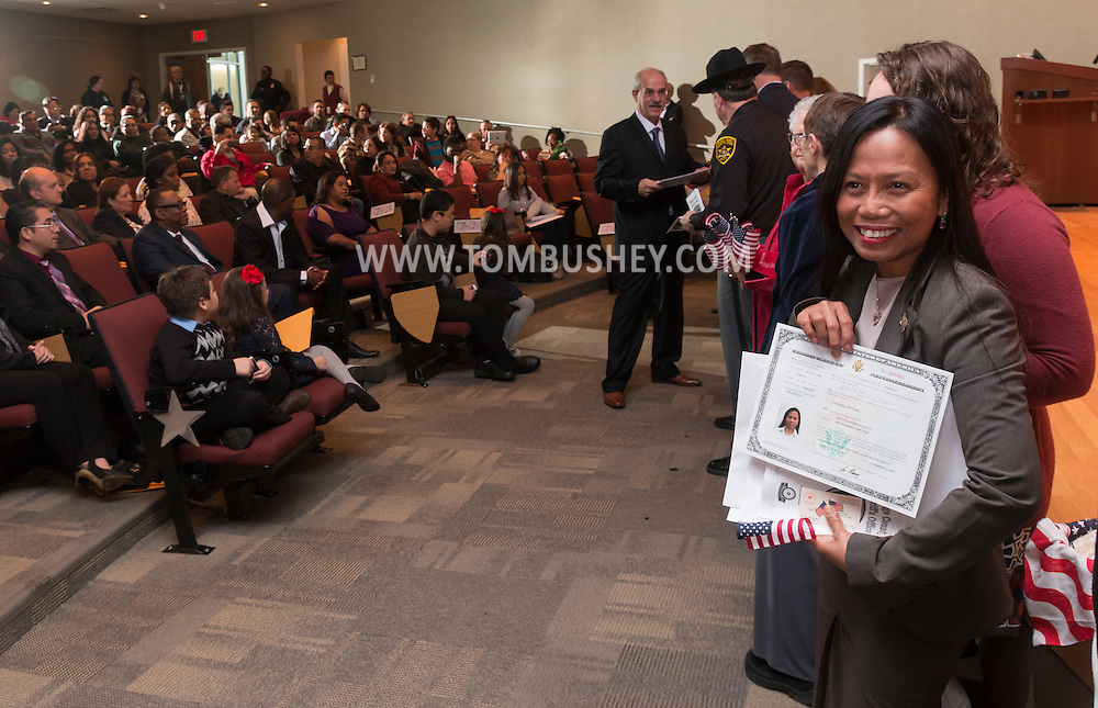 Goshen, New York - A woman poses for a photograph during a Naturalization ceremony at the Orange County Emergency Services Center on Nov. 17, 2016.