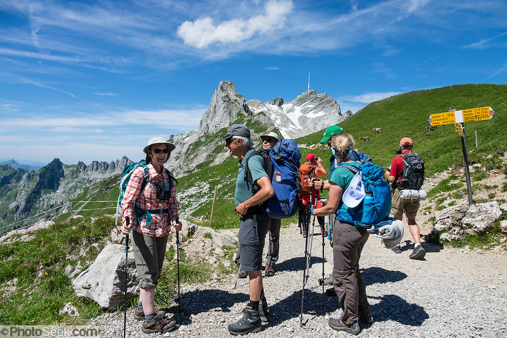 Hikers at Rotsteinpass (2120 m) in Switzerland, Europe. In the background, a transmission tower caps Säntis (2502 m), the highest mountain in the Alpstein massif of northeastern Switzerland, and highest of the Appenzell Alps. Appenzell Innerrhoden is Switzerland's most traditional and smallest-population canton (second smallest by area). For licensing options, please inquire.