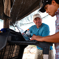 Jorge Caballero Espejo, Drone and GIS Coordinator at CINCIA, (black hat) preparing flight plans for CINCIA's fixed-wing drone with Wake Forest University biology professor, Dr. Miles Silman. Following Peru's February 2019 militarized crackdown on illegal and unofficial alluvial gold mining in the La Pampa region of Madre de Dios, Wake Forest University's Puerto Maldonado-based Centro de Innovación Científica Amazonia (CINCIA), a leading research institution for the development of technological innovation for biological conservation and environmental restoration in the Peruvian Amazon, is applying years of scientific research and technical experience related to understanding mercury contamination and managing Amazonian ecosystems. What they learn will help guide urgent remediation, restoration, and reforestation efforts that can also serve as models for how we address the tropic's most dramatically devastated landscapes around the world. La Pampa, Madre de Dios, Peru.