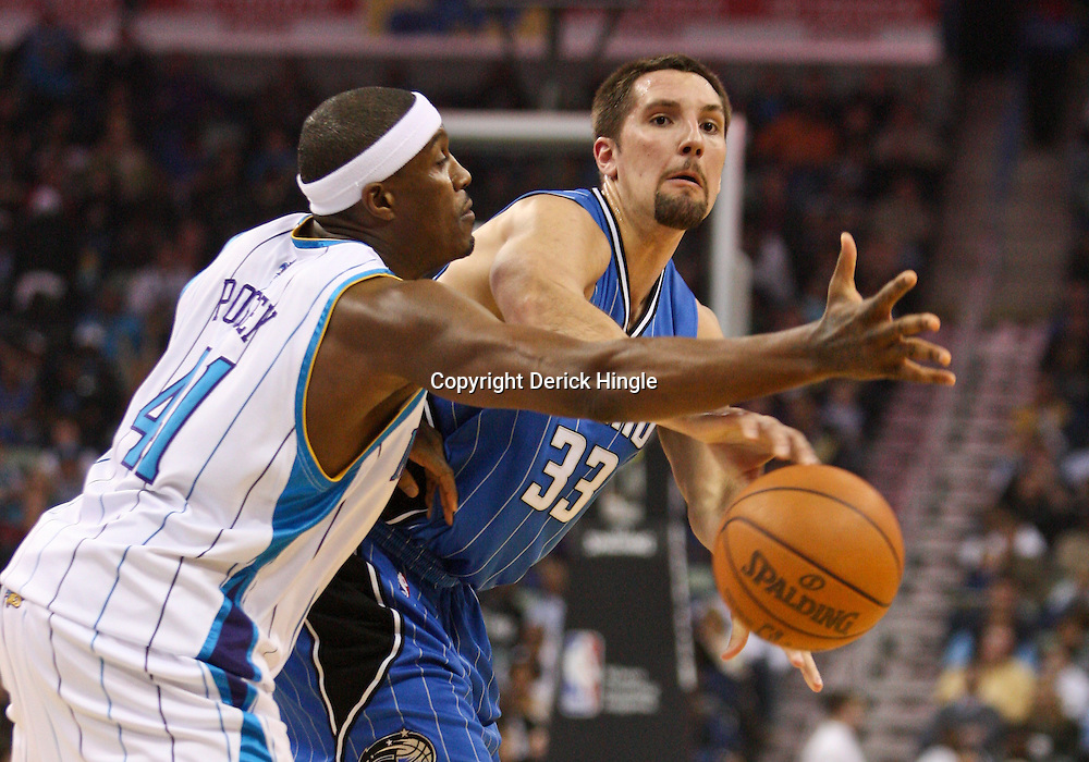 Feb 26, 2010; New Orleans, LA, USA; Orlando Magic forward Ryan Anderson (33) passes the ball past New Orleans Hornets forward James Posey (41) during the first half at the New Orleans Arena. Mandatory Credit: Derick E. Hingle-US PRESSWIRE