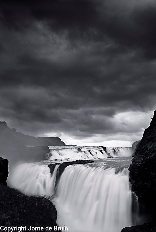 The Gullfoss (Golden Falls) Waterfall in Iceland under a dark sky.