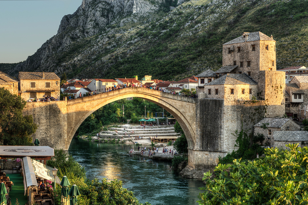 "Literally the point where Christian culture met the Ottoman Empire in Mostar, the Old Bridge (Stari Most) was commissioned by Suleiman the Magnificent in 1557.  It is guarded by the Halebija Tower (left) and the Tara Tower (right), collectively known as the ""bridge keepers"" or mostari, giving the town of Mostar its name."