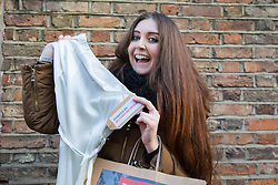 © licensed to London News Pictures. London, UK 22/11/2013. Ahoushka Wilson celebrating after buying a dress donated by Victoria Beckham to help raise money for Philippine typhoon disaster at the British Red Cross branch in Chelsea, London. Photo credit: Tolga Akmen/LNP