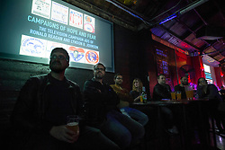 Patrons enjoy a tasty beverage while watching a presentation on presidential campaign propaganda at the once-monthly Nerd Nite event, Monday, April 24, 2017, at Club 21 in the Uptown neighborhood of Oakland, Calif. (Photo by D. Ross Cameron)