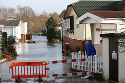 © Licensed to London News Pictures. 06/01/2014, Christchurch, UK. A resident watches the streets flooded by the overflow River Stour at Iford Bridge, Christchurch, England , Monday, Jan. 6, 2014. Part of UK continue to be affected by floods and strong wind. Photo credit : Sang Tan/LNP