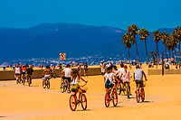 People riding bikes along the Ocean Front Walk at Venice Beach, Los Angeles, California USA.