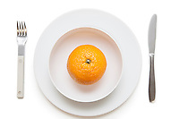 High angle view of an orange in dish with fork and knife over white background