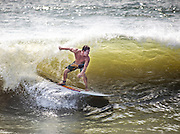 A surfer takes advantage of the ocean swell generated by a passing hurricane along the South Carolina coast in Isle of Palms, SC