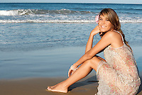 Young woman in summer dress sitting on beach side view