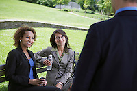 Two business women sitting on park bench looking at businessman