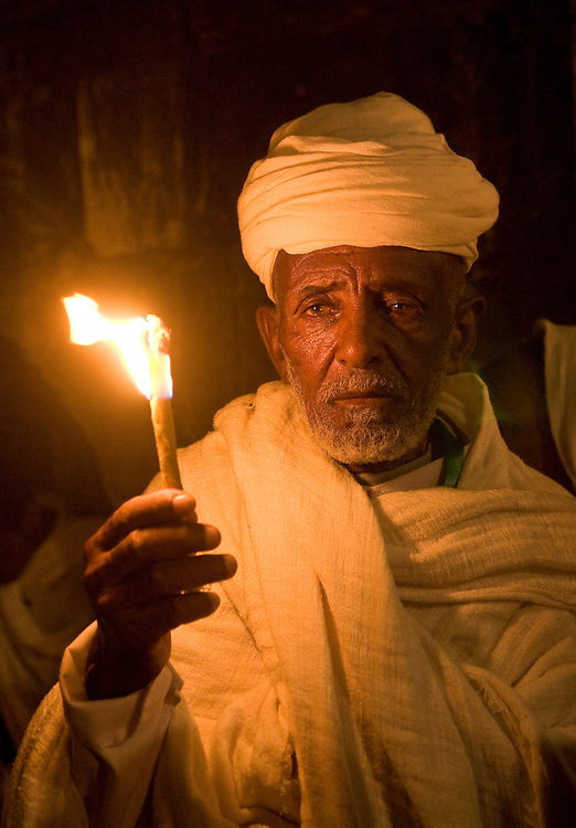 JERUSALEM - APRIL 14 : Ethiopian Orthodox worshiper hold candle during the Holy fire ceremony at the Ethiopian section of the Holy Sepulcher in Jerusalm Israel on April 14 2012