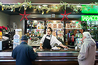 "NAPLES, ITALY - 12 DECEMBER 2014: Ciro Pipolo, a 45 years old barista, serves clients at Bar Settebello, a cafè that is part of the ""Rete del Caffè Sospeso"" (Suspended Coffee Network) in Naples, Italy, on December 12th 2014.<br /> <br /> A caffè sospeso,or suspended coffee, is a cup of coffee paid for in advance as an anonymous act of charity. The tradition began in the working-class cafés of Naples, where someone would order a sospeso, paying the price of two coffees but receiving and consuming only one. A poor person enquiring later whether there was a sospeso available would then be served a coffee for free."