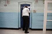 A prison officer checks the cell of a prisoner on E wing. HMP Wandsworth, London, United Kingdom