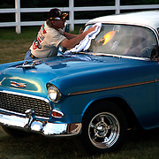 Joe Kopp, from Rochester, Mn., wipes the windshield of his 1955 BelAir at the Iowa State Fairgrounds...  The cars and their owners were in Des Moines over the 4th of July weekend for the Good Guys 16th Heartland Nationals held at the Iowa State Fairgrounds, bringing over 3,500 of the country?s hottest rods and coolest customs to Iowa?s Capital City.  ..Exhibitors are very skilled, multi-talented craftsmen. They dedicate thousands of hours to bring their hot rod or custom  autos to a high standard. Unlike many car shows the Good Guys usually drive both to and from the event...Photo by David Peterson