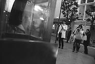 Pedestrians photograph a shop dummy hanging in a display case, Shibuya, Tokyo, Japan. 2004