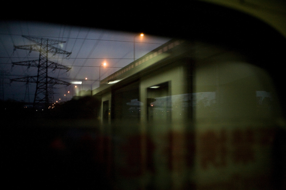 Near Changsha at night, reflection of the corridor and an highway on a window of the train to Beijing.