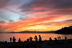 Visitors and locals take in the sunset from English Bay Beach Park in Vancouver, British Columbia. The popular beach, also called First Beach, is located in the most populated beach area in downtown Vancouver. The Stanley Park Seawall, a popular running and biking route, runs along the east side of the beach.