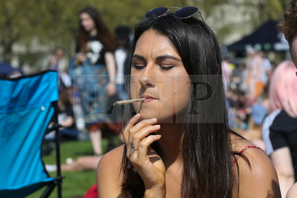 © Licensed to London News Pictures. 20/04/2019. London, UK. A woman smokes cannabis as thousands of revellers gather in London's Hyde Park as part of '4/20 Day', an unofficial International Weed Day, an event that takes place every year on 20 April for people to smoke cannabis without been detained. Attendees are calling on the Government to decriminalise Class B drug and raise awareness about the drug. Photo credit: Dinendra Haria/LNP