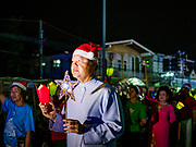 """23 DECEMBER 2018 - CHANTABURI, THAILAND: A priest leads the procession at the Cathedral of the Immaculate Conception's Christmas Fair in Chantaburi. Cathedral of the Immaculate Conception is holding its annual Christmas festival, this year called """"Sweet Christmas @ Chantaburi 2018"""". The Cathedral is the largest Catholic church in Thailand and was founded more than 300 years ago by Vietnamese Catholics who settled in Thailand, then Siam.   PHOTO BY JACK KURTZ"""