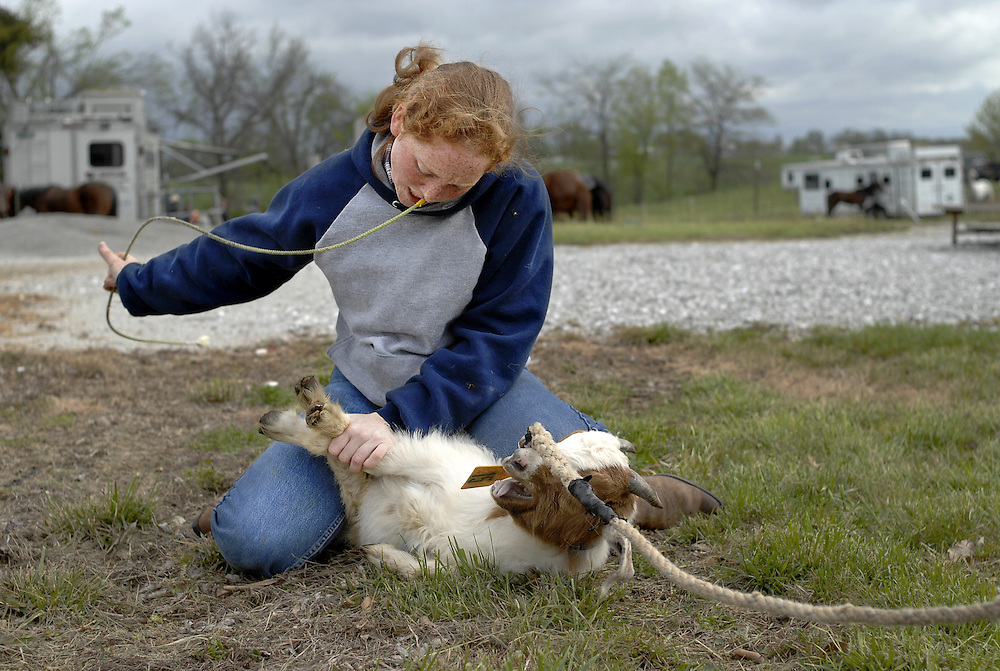 Casey Chasteen, 18, is a two-time Missouri state champion in goat tying. The Rock Bridge High School senior is up early on a Saturday. Most of her classmates are probably sleeping in, especially on this cold, windy spring morning, but for Casey every weekend is another rodeo.<br /> <br /> Her smile is bright under a small straw hat. Her red hair bobs in the wind. She has big responsibilities. As state champion, Casey is the event director for goat tying. She makes sure the animals have been properly vetted, tied three times and organized by size.<br /> <br /> As part of this process, participants each take a turn tying a goat at the end of a lead line. Casey helps the others as they practice. She likes to teach, likes the challenge of shaving seconds off a time, even though these are her competitors.<br /> <br /> She's fast and fluid with a tie -- one end of the string tucked in a belt loop, the other end in her mouth. In a blur of motion, the goat is upended and three legs are bound together. When a tie goes wrong and the goat pulls free, Casey goes through the motions again, slower this time, correcting in her mind the missed step.<br /> <br /> She gently rolls the animal onto each side, teaching it the futility of struggle. She rubs its soft ears and hairy chest, a kindness the other teens don't share. &quot;It's just a goat, Casey,&quot; one girl says.<br /> <br /> &quot;I know,&quot; Casey replies as she gently unties the animal.<br /> <br /> &quot;You have to set an example for the younger kids,&quot; she explains later.<br /> <br /> Before competition, she is focused. Her peers are chatting and flirting, waiting for their events, and Casey sits apart. &quot;Sometimes I get to where I just have to think it all through. I do my own thing.&quot; She watches the other competitions. She checks out her draw. She goes through the steps in her mind. She might be set apart from the crowd, but &quot;doing her own thing&quot; is what has made her exceptional. It's what'