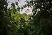 The English flag flies in the churchyard of St Dunstan church, West Peckham, Kent.