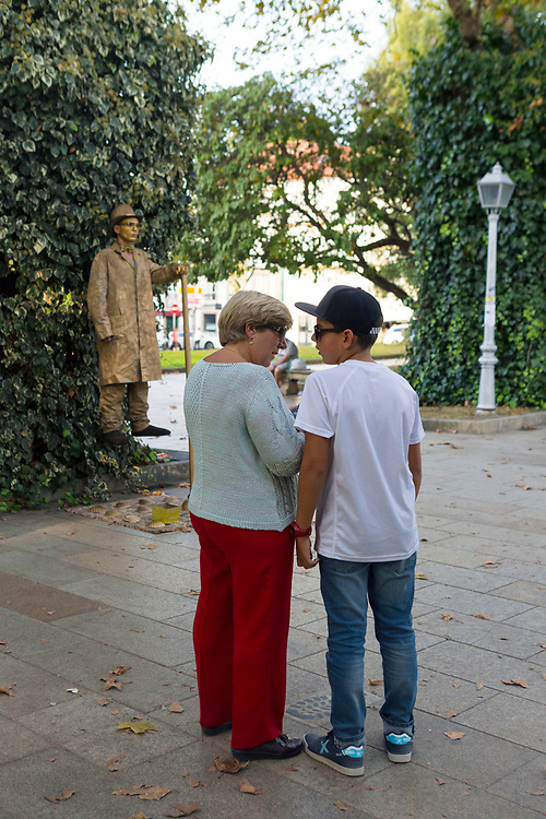 SANTIAGO DE COMPOSTELA, SPAIN - 14th October 2017 - Mother and son discuss how a living statue performer might be creating the spectacle of floating in mid air at Alameda Park, Santiago de Compostela, Galicia, Spain.