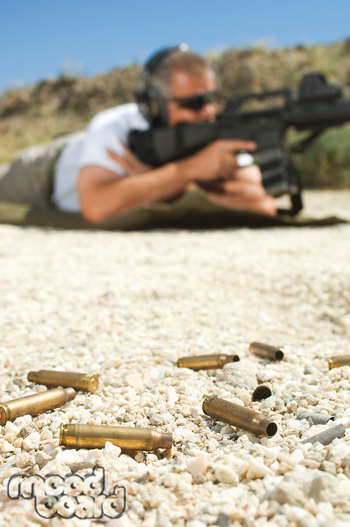 Man aiming machine gun at firing range, focus on bullets in foreground