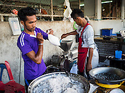 18 JUNE 2015 - PATTANI, PATTANI, THAILAND: Men make fresh coconut milk by combining ground up coconut and water in the market in Pattani. Many Thai Muslims go shopping early in the day to buy food for Iftar, the meal that breaks the day long Ramadan fast.    PHOTO BY JACK KURTZ