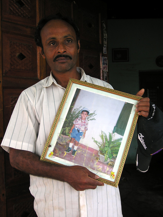 Laurance Sindateri holds a picture of his son that he has recovered from his ruined home. His son was killed along with Laurance's father by the Tsunami that struck S.E. Asia following a 9.0 earthquake in the Indian Ocean, .Batticaloa, Sri Lanka. 11/01/2005.Photo © J.B. Russell