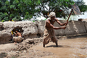 A family elder digs in the floodwater to reinforce the walls and boundaries of his families compound in Muzzafargarh. ..Residents of outlying villages in the district of Muzzafargarh continue to evacuate villages as flood waters continued to cause havoc in South Punjab...