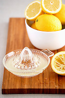Bowl of lemons and juicer on cutting board